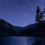 A long exposure captures star trails in the sky above Cathedral Lakes Lodge.